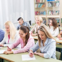 Attentive adult students industriously writing down the summary in classroom